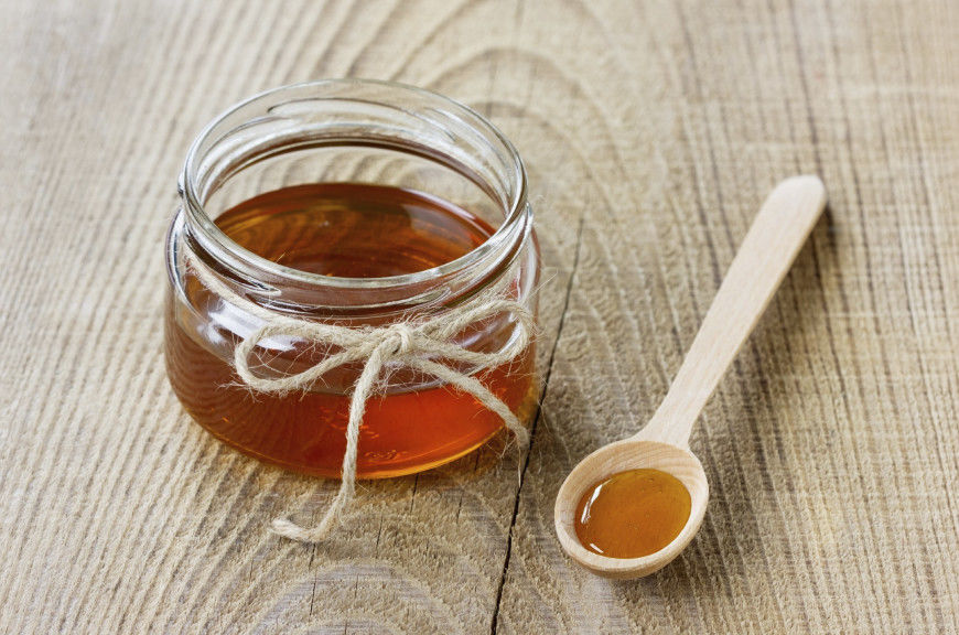 Honey in a wooden spoon and jar on a wood rustic background